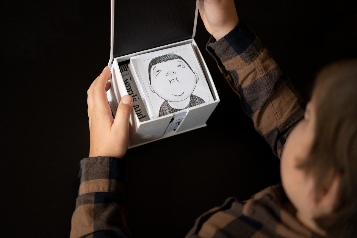 Product photography of the Face it Card with a boy opening the box  and looking at an illustrated face of a happy boy.