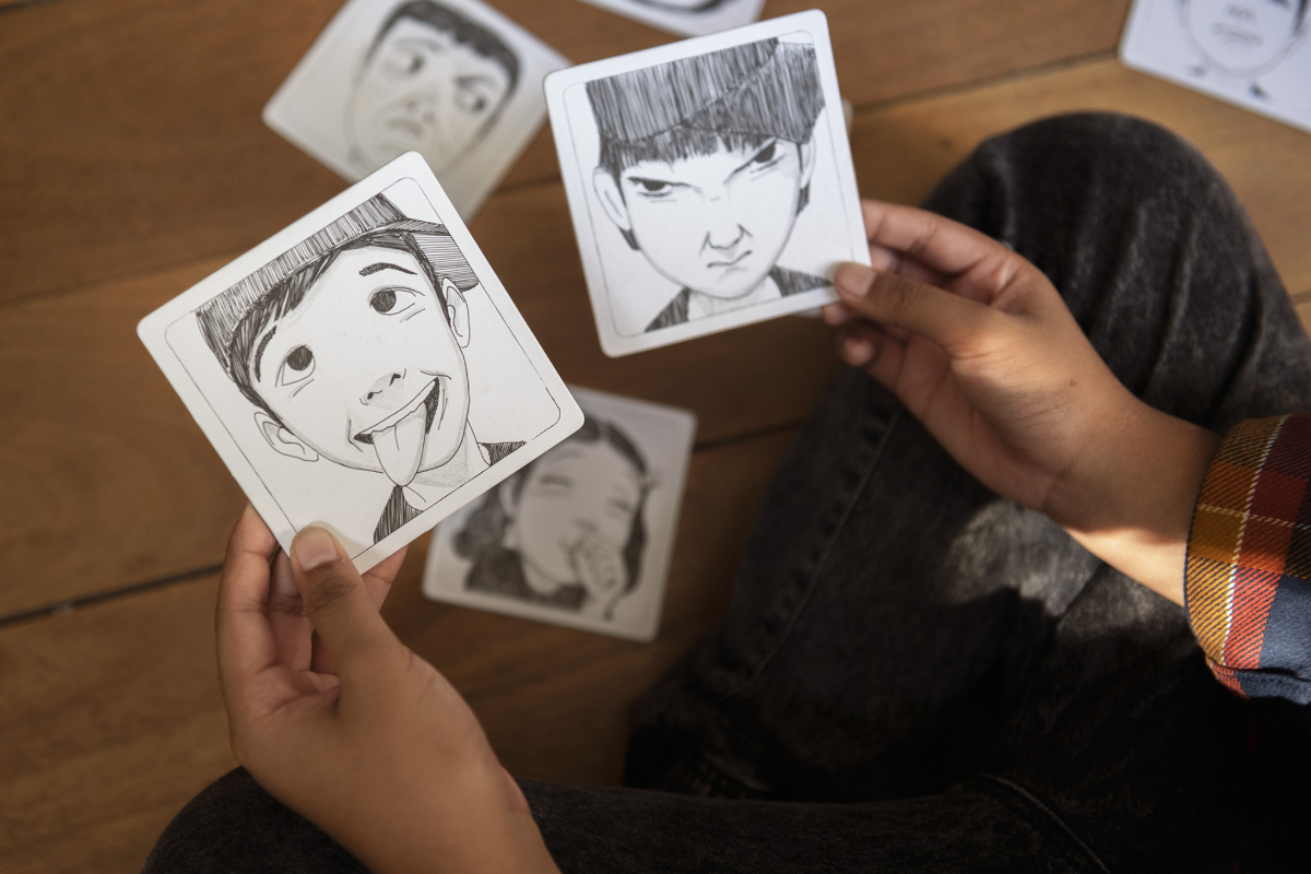 Product photography of the Face it Card with a boy handling two coster sized cars with two illustrated facial expressions.
