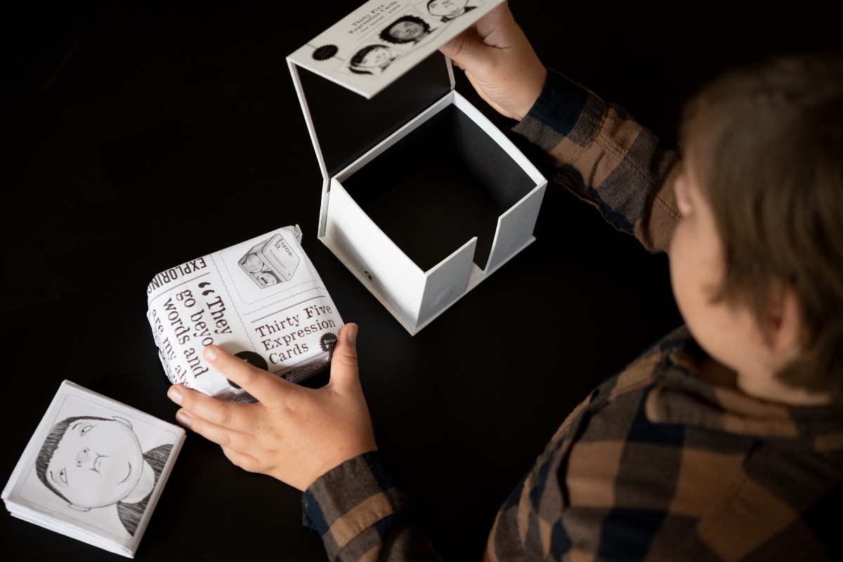 Product photography of the Face it Card with a boy opening the box  and unpacking it
