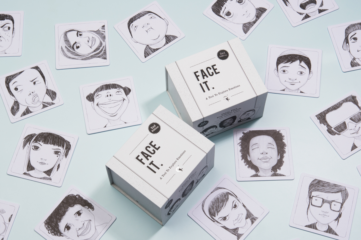 Product photography of the Face it Cards. Close back and white photo of a square box with the title Face It next to some craft material.