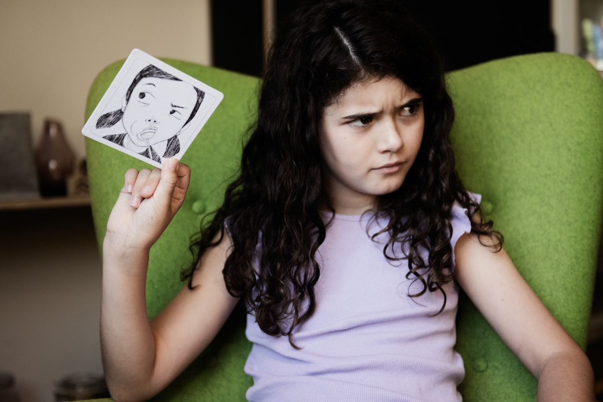 Product photography of the Face it Card with a angry looking girls holding a coster sized illustrated image of a angry looking facial expression.