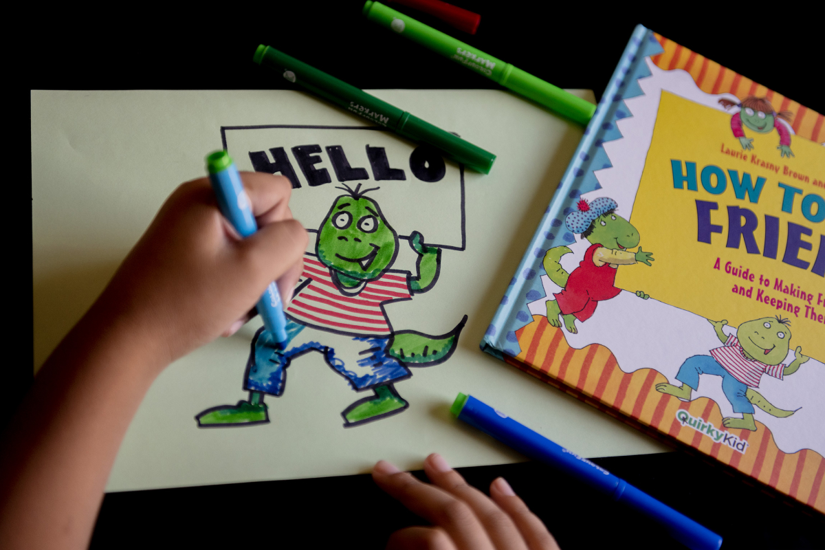 Product Photograph of the How to be a Friend by Quirky Kid showing the hands of a child copying the cover of the book - a dinosaur holding a sign.