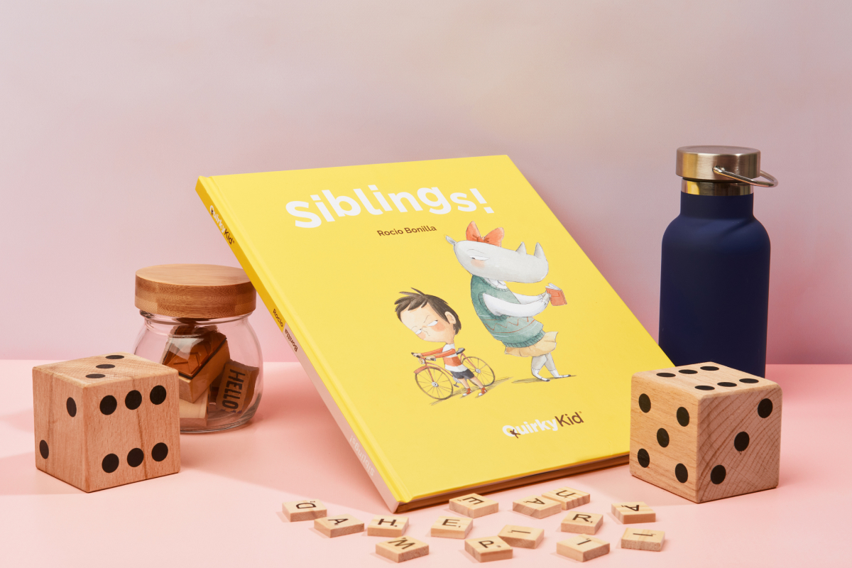 Product photography of the book siblings by Quirky Kid showing the book in a styled table next to some wooden dices.