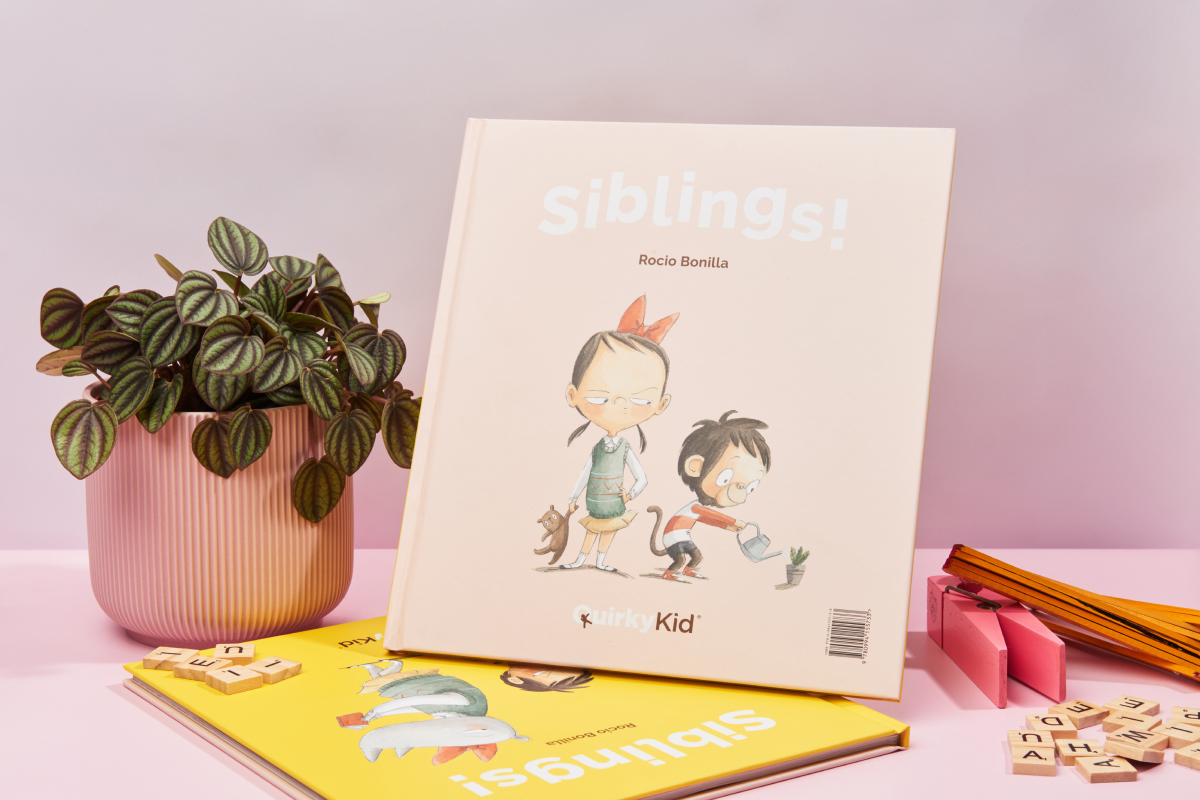 Product photography of the book siblings by Quirky Kid showing the book in a styled table next to some large pegs and a pink pot plant d=holding a green  plant.
