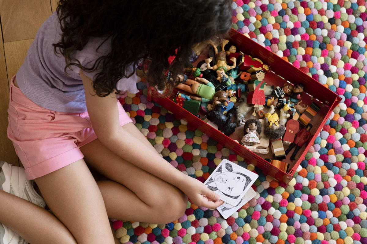 A girl sitting on the floor  playing with a two of  coster card with the illustrations of the Face It cards by Quirky Kid