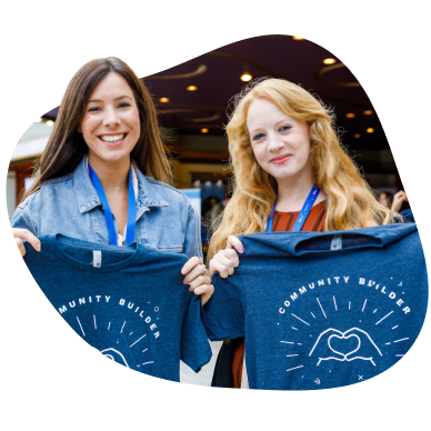 """Two women holding up """"community builder"""" t-shirts"""