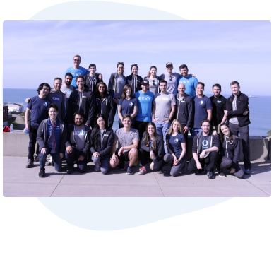 27 people standing in front of an ocean background, wearing Bevy t-shirts