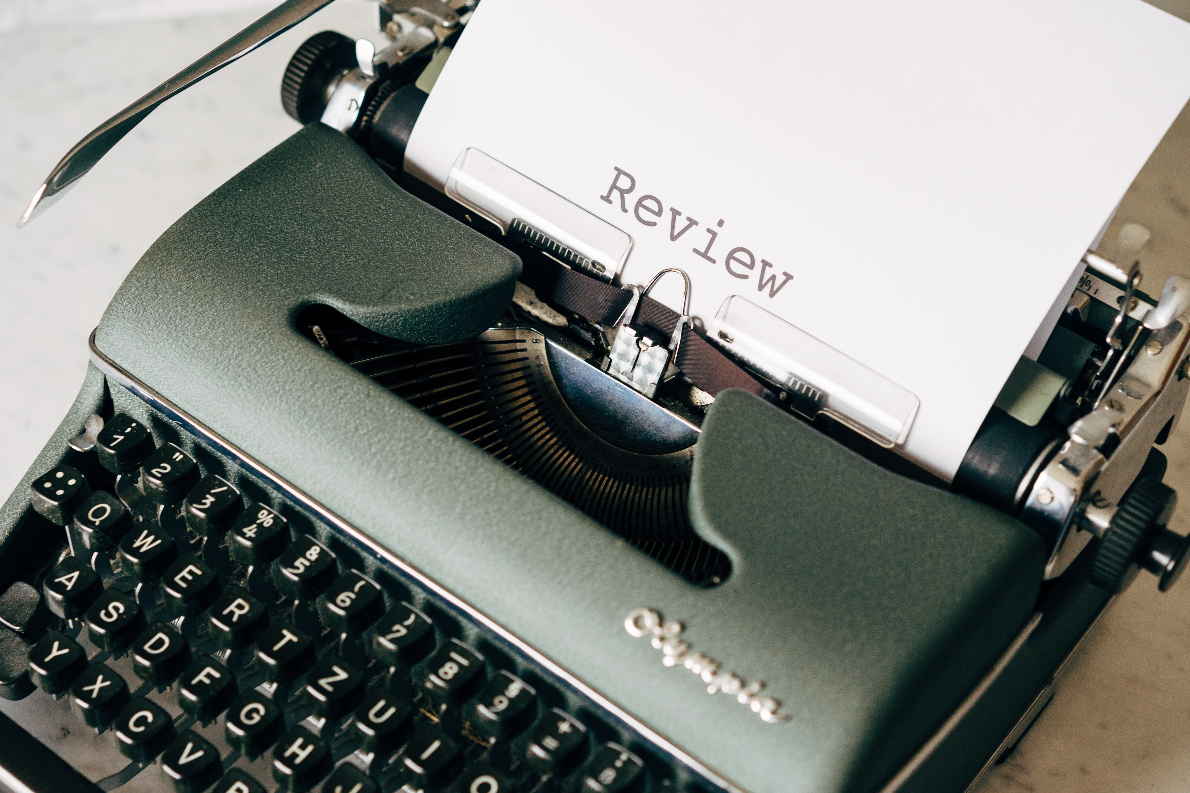 A green old-fashioned typewriter, with the word 'review' written out onto a page in large lettering.