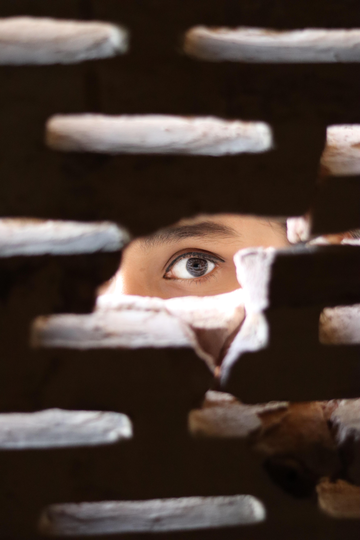woman peering through gap in a wall.