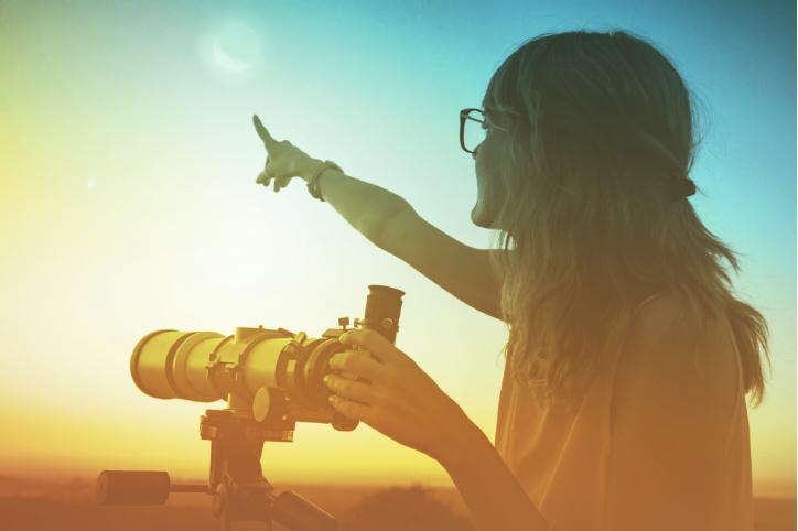 Woman using telescope at sunset.