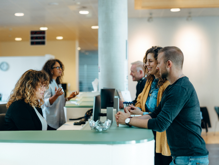 People gathered around the front desk of a corporate building