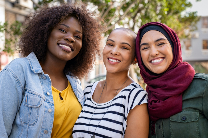 Three diverse young women standing side-by-side and smiling