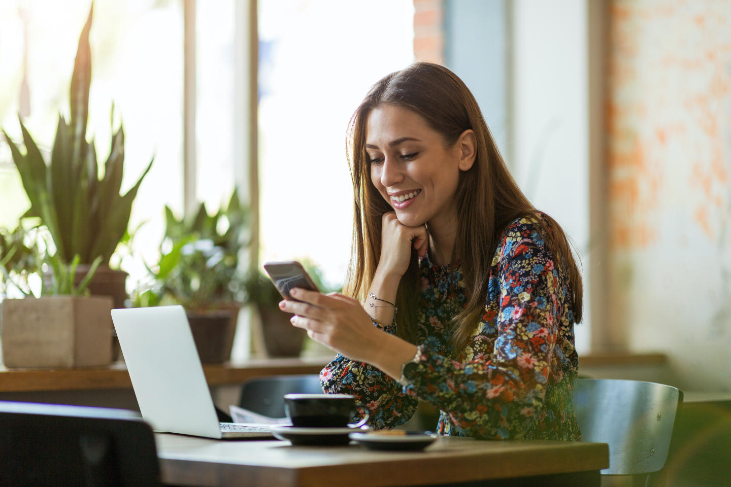 Woman checking her cell phone and smiling at a coffee shop