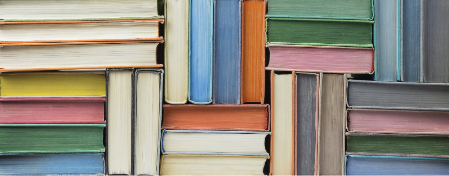 Many colorful books stacked up against each other