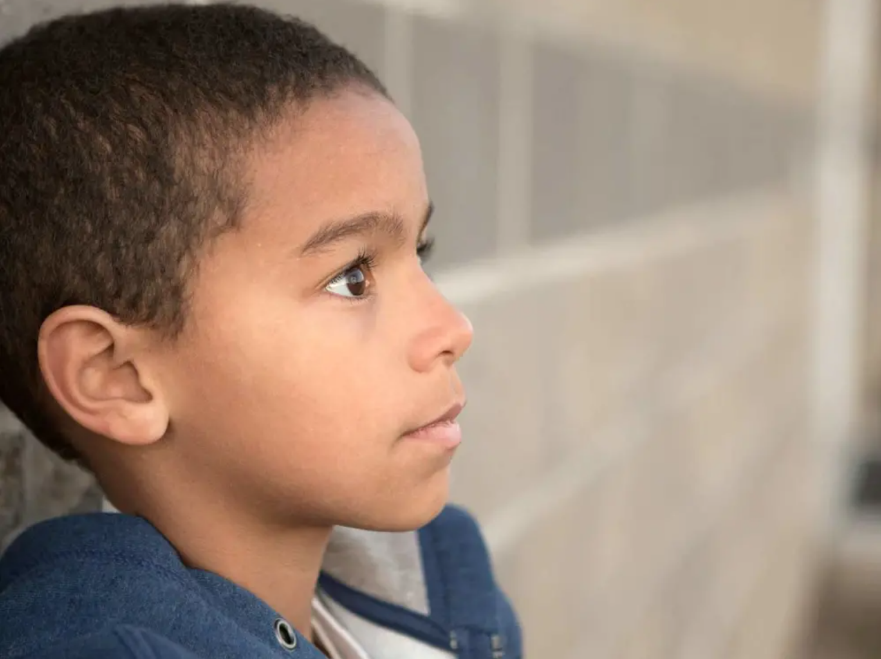 A young boy leaning against a brick wall looking worried