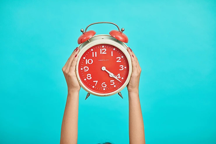 Vintage red alarm clock being held up by two hands