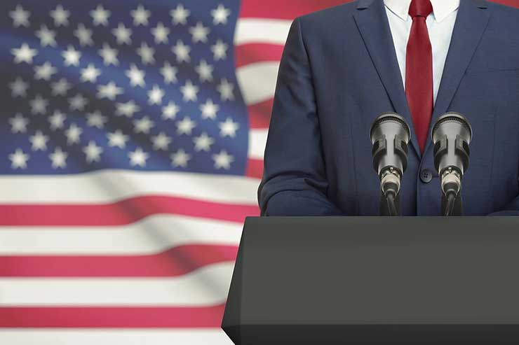 Politician speaking at the podium with the United States of America flag behind them