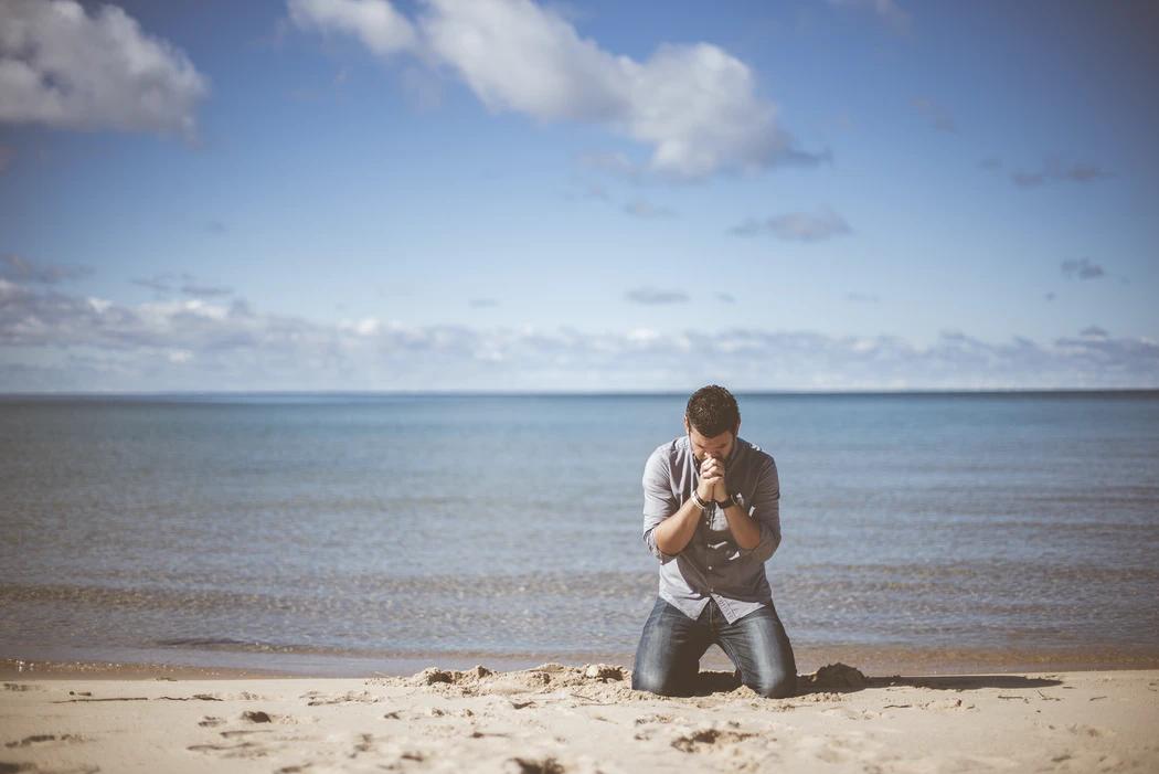A man prays on a beach