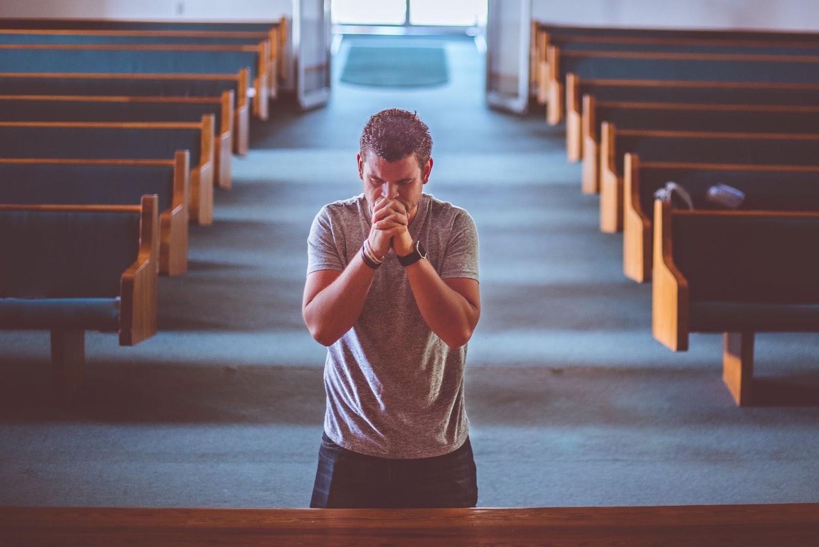 A man kneels in prayer in a church