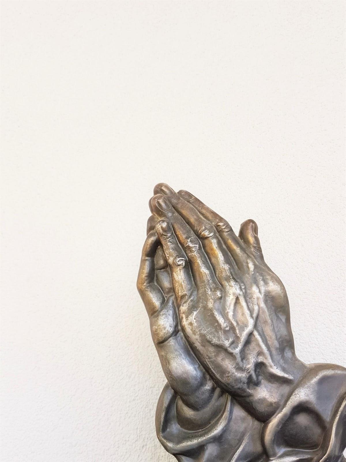 metal hands in prayer