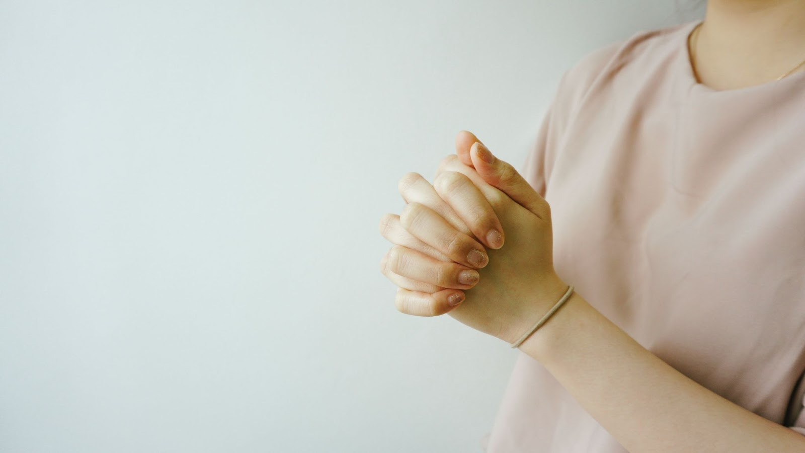 two hands of a person clasped in prayer