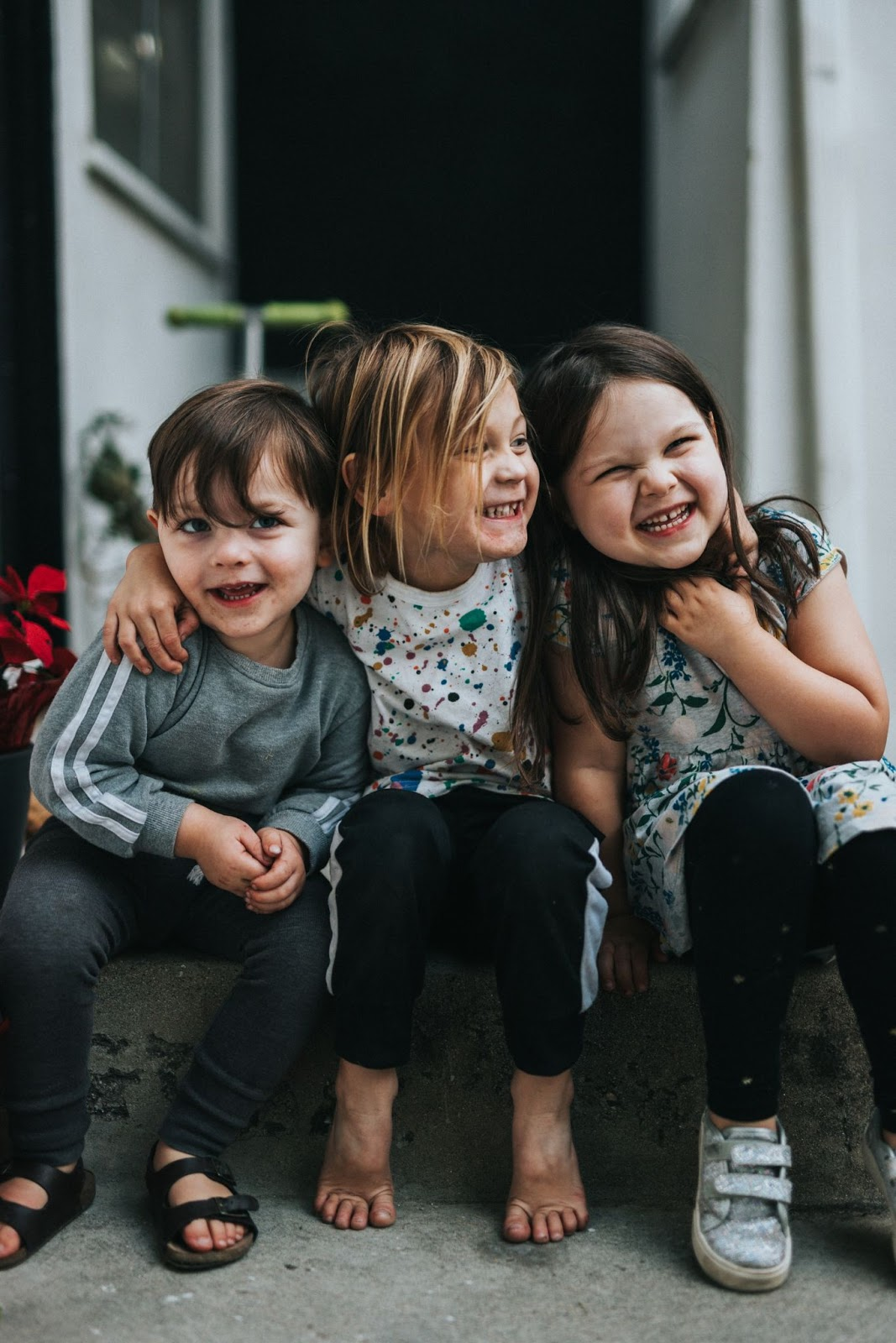 three children sitting down on a stoop and hugging