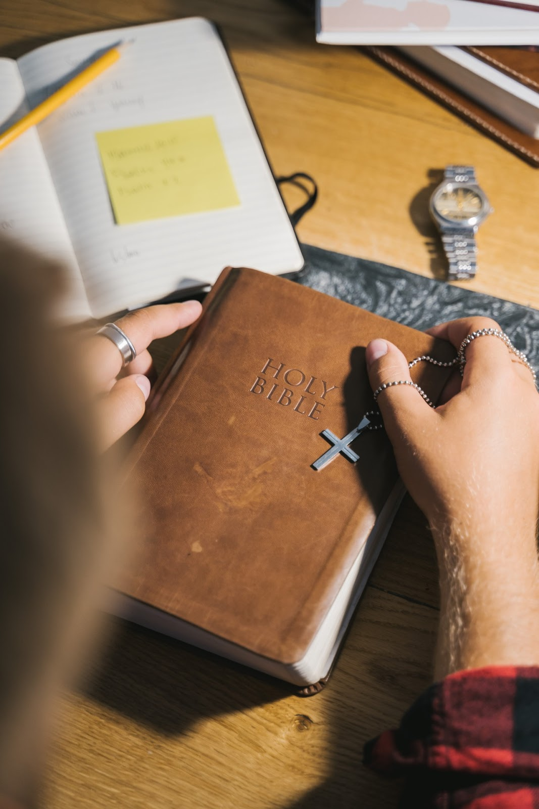 person holding a bible and a cross