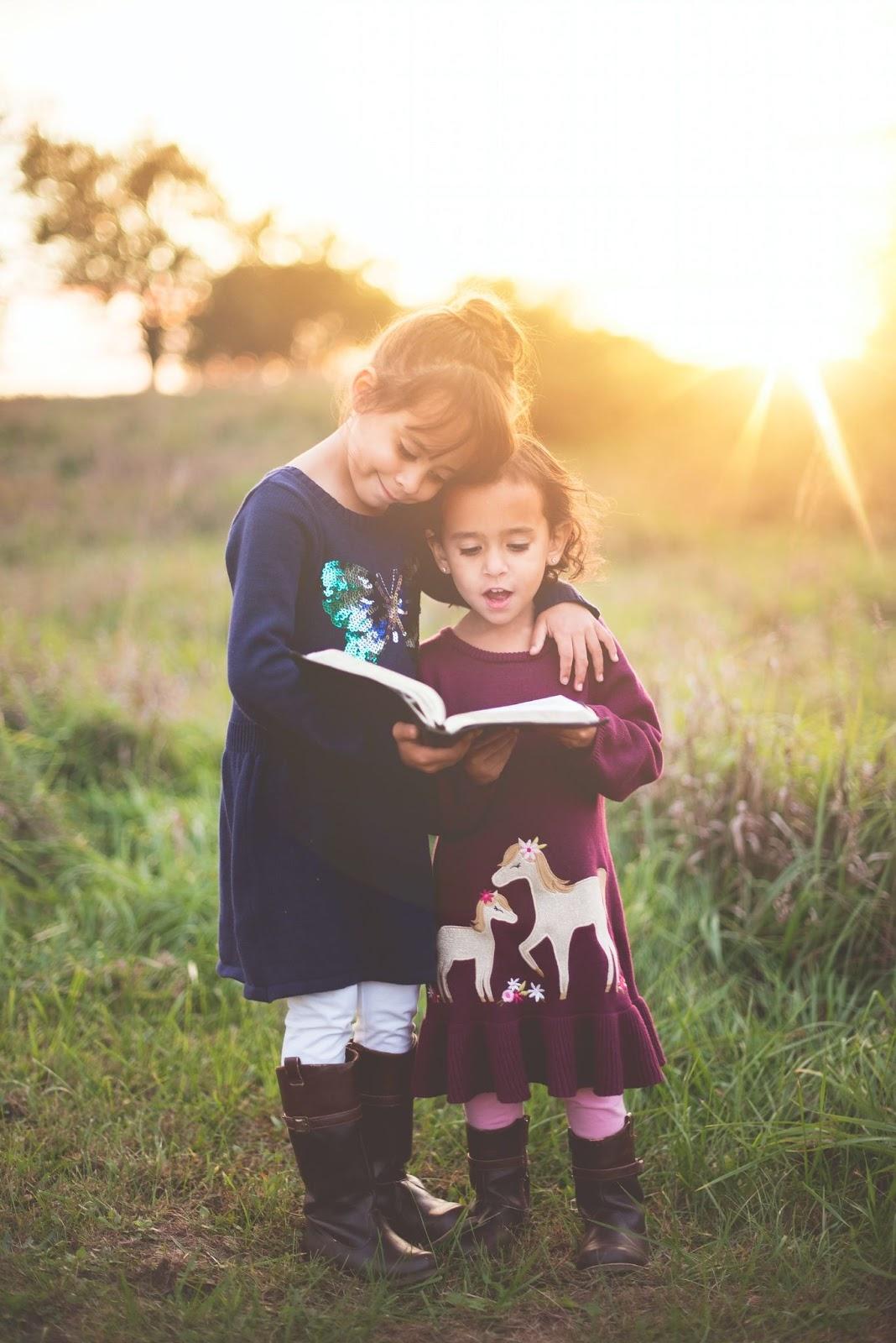 two little girls reading a Bible in a field