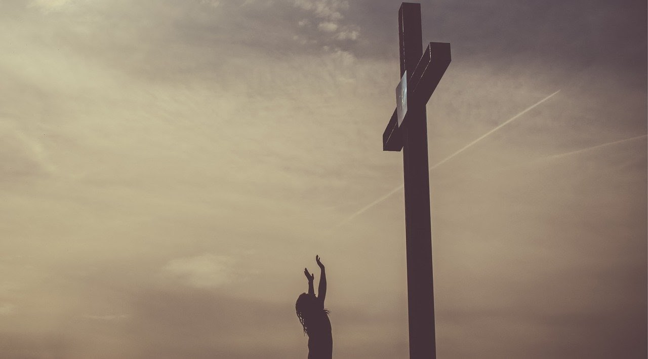 Woman hands raised to a cross