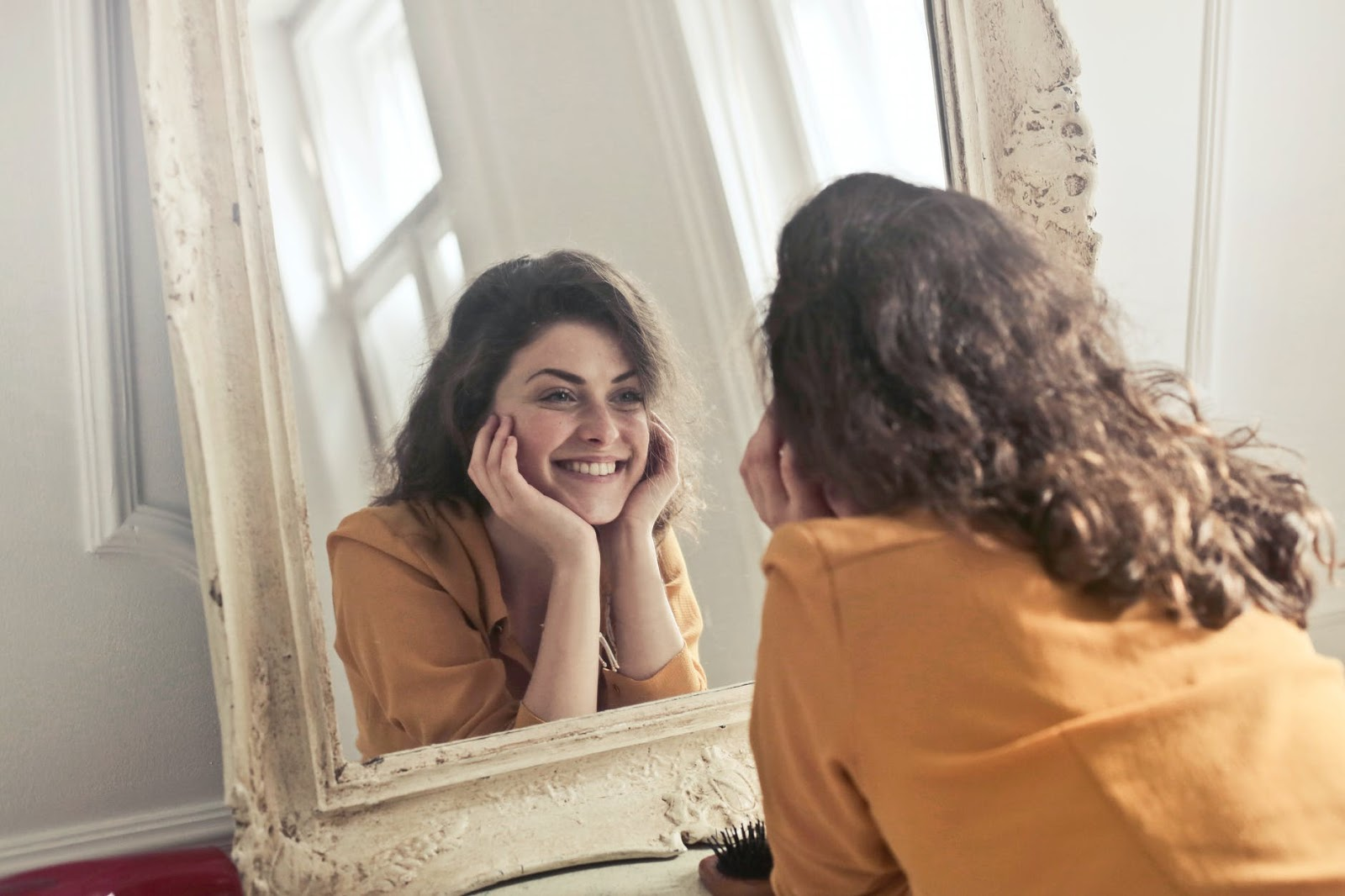 A woman looks into a mirror