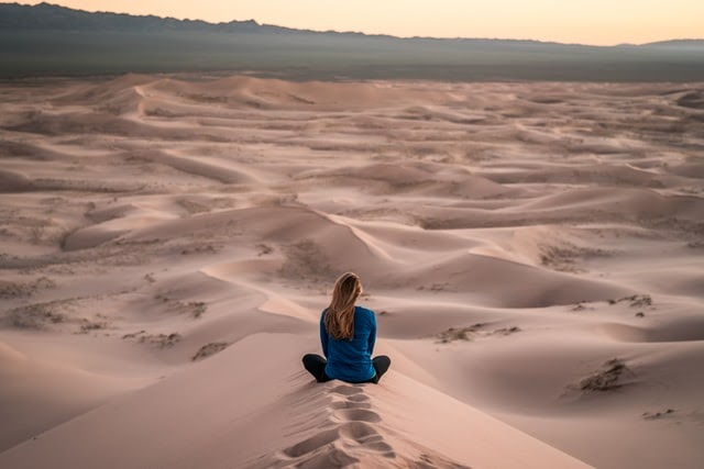 Woman sitting in sand dunes in quiet reflection.