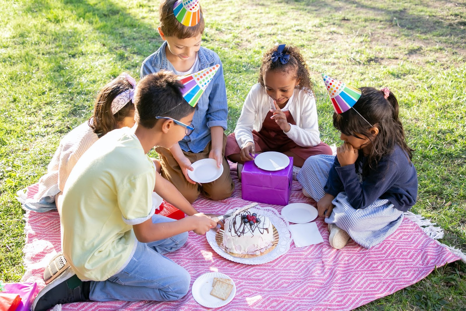 Children sit on a blanket outside and cut into a birthday cake