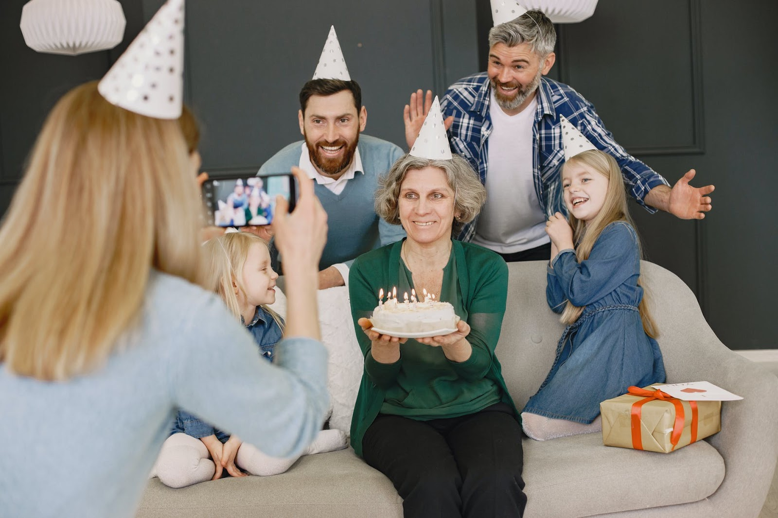 Family poses for a picture with party hats and a birthday cake