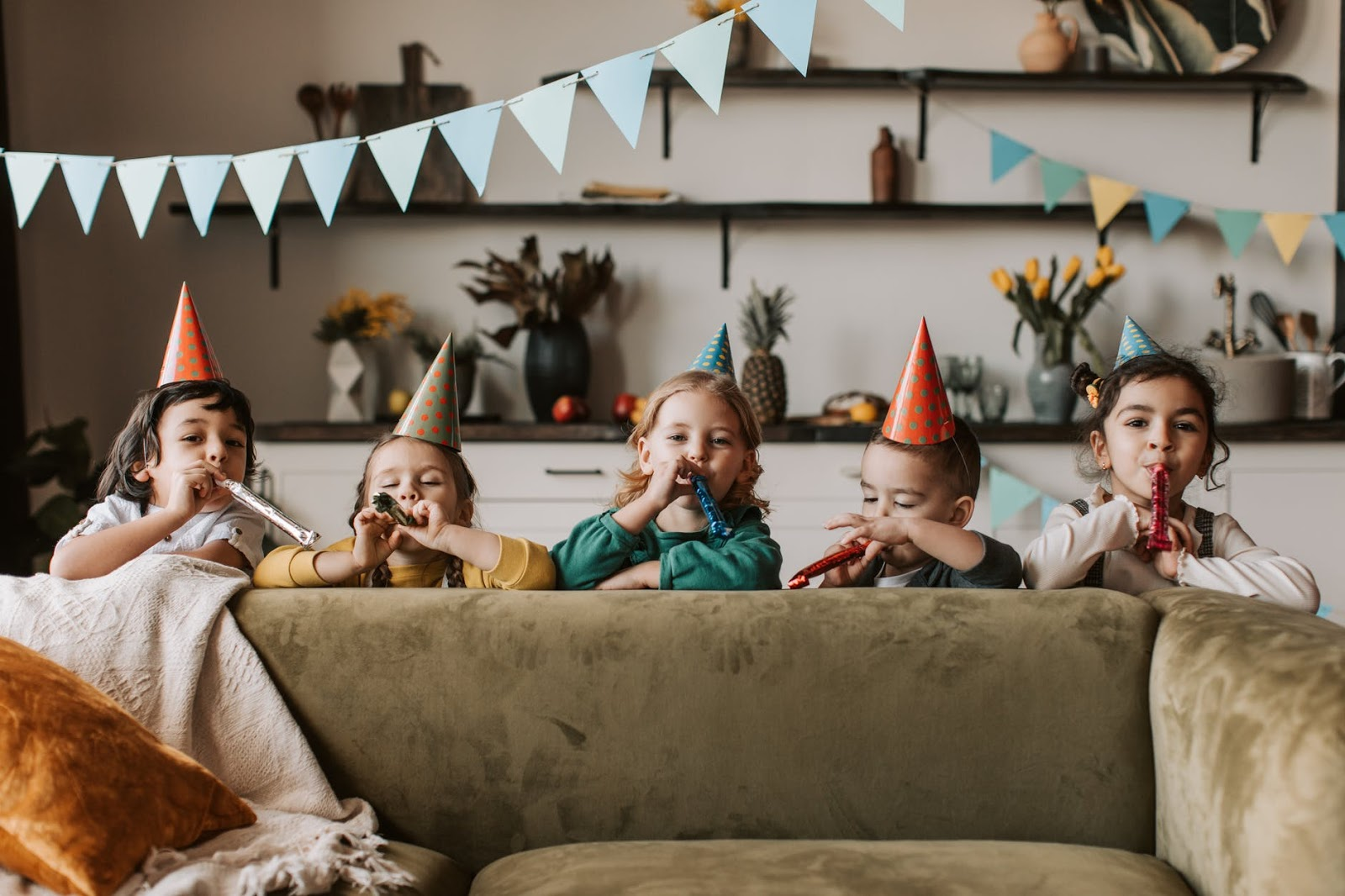 Five children stand behind couch with birthday decorations