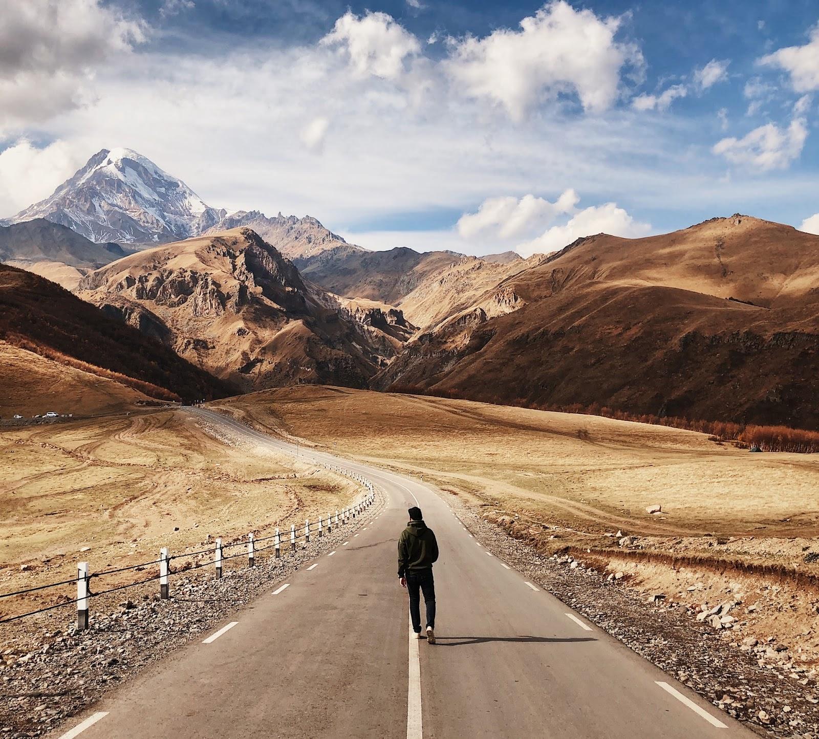 man walking on a road