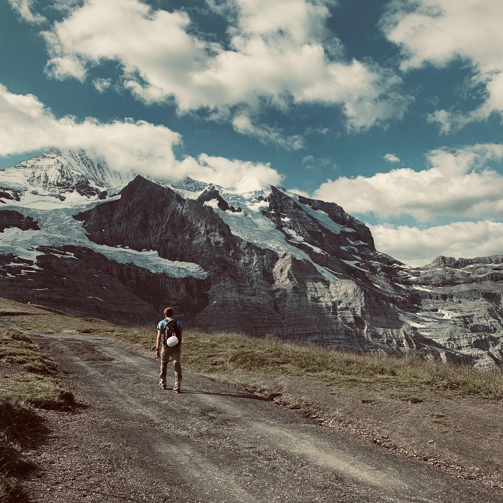 man walking next to mountains