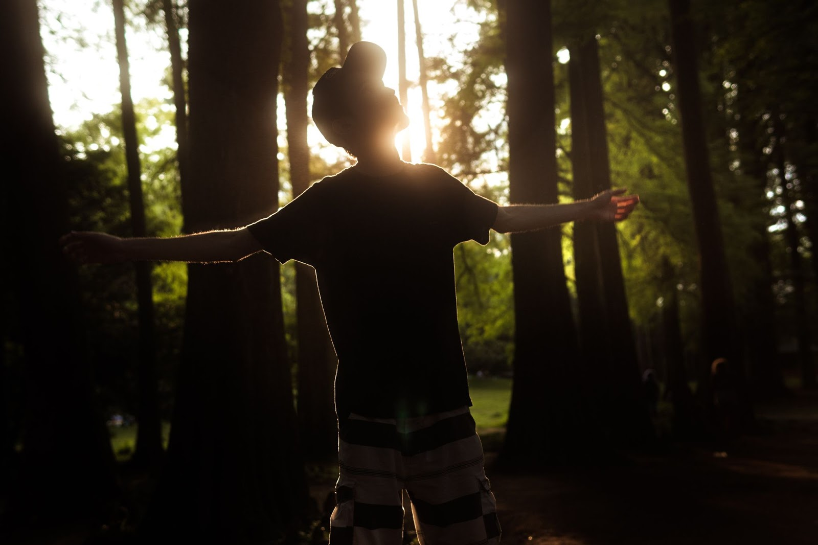 Man standing outside with arms stretched toward heaven.