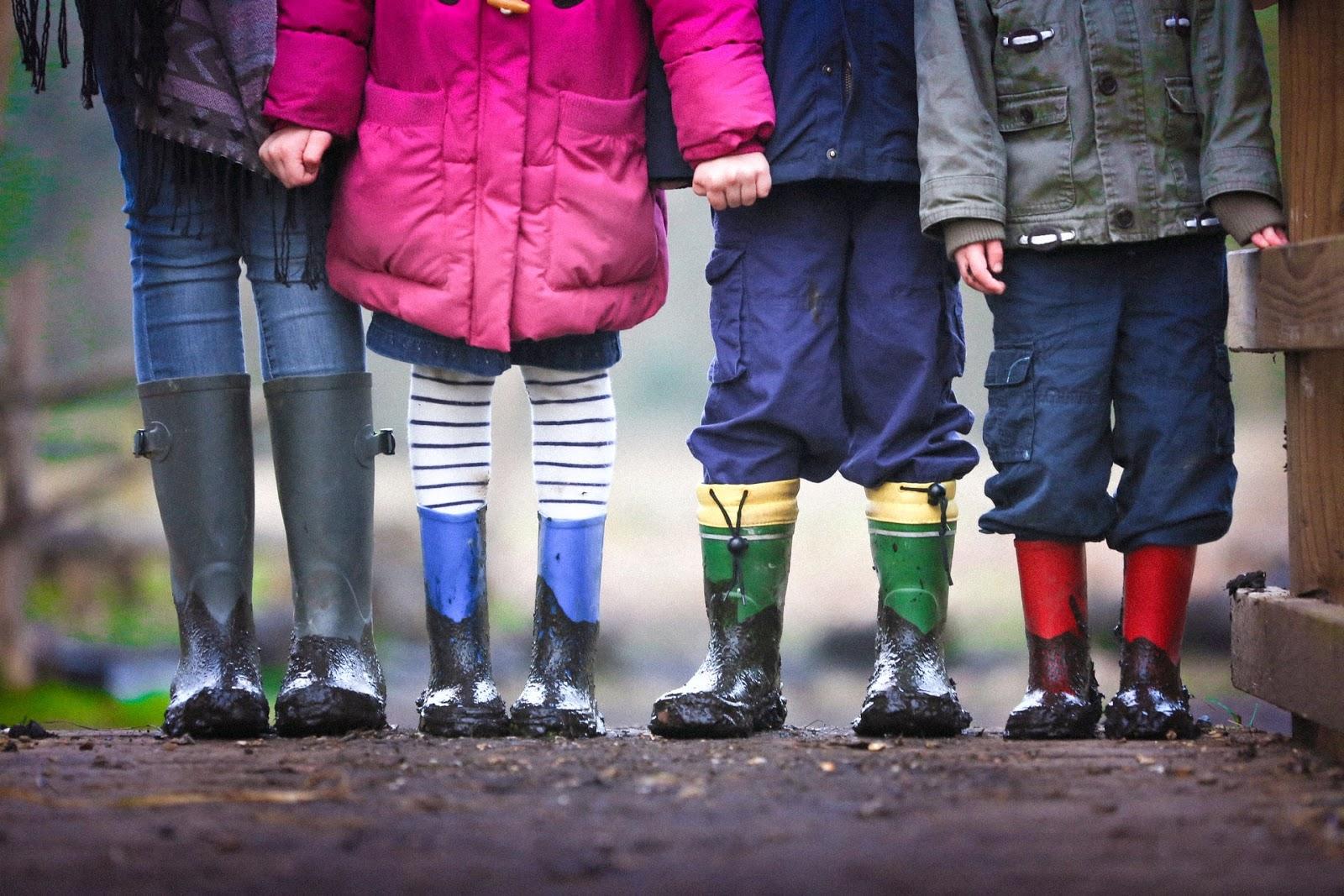 four children in rain boots holding hands