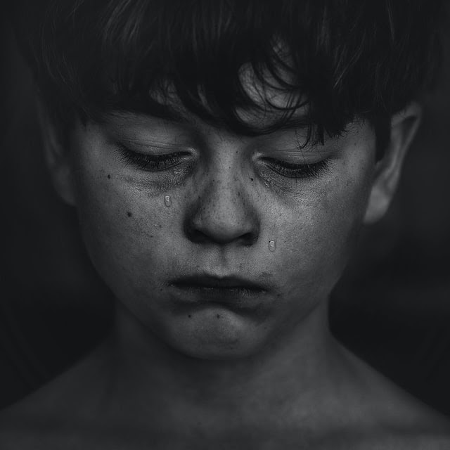 Boy with tears streaming down face