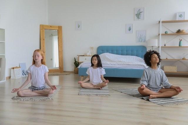 Three children meditating together