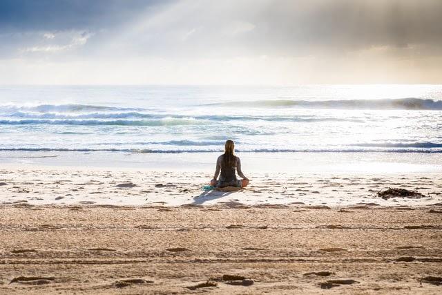 Woman meditating near ocean