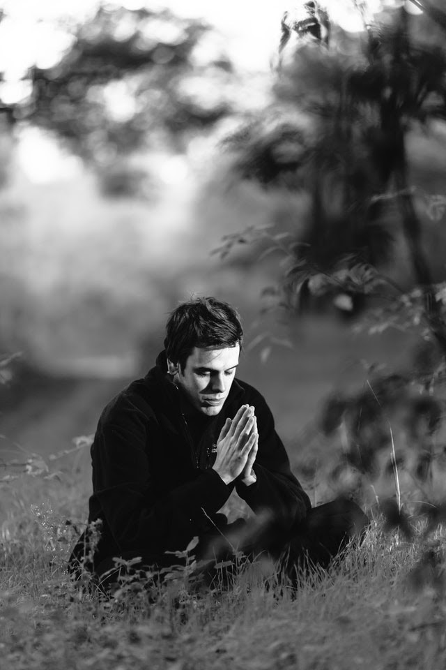 Young man meditating in a field, hands clasped in prayer
