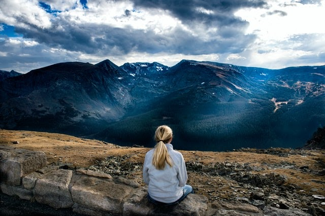 Woman sitting on a rock overlooking a high mountain view