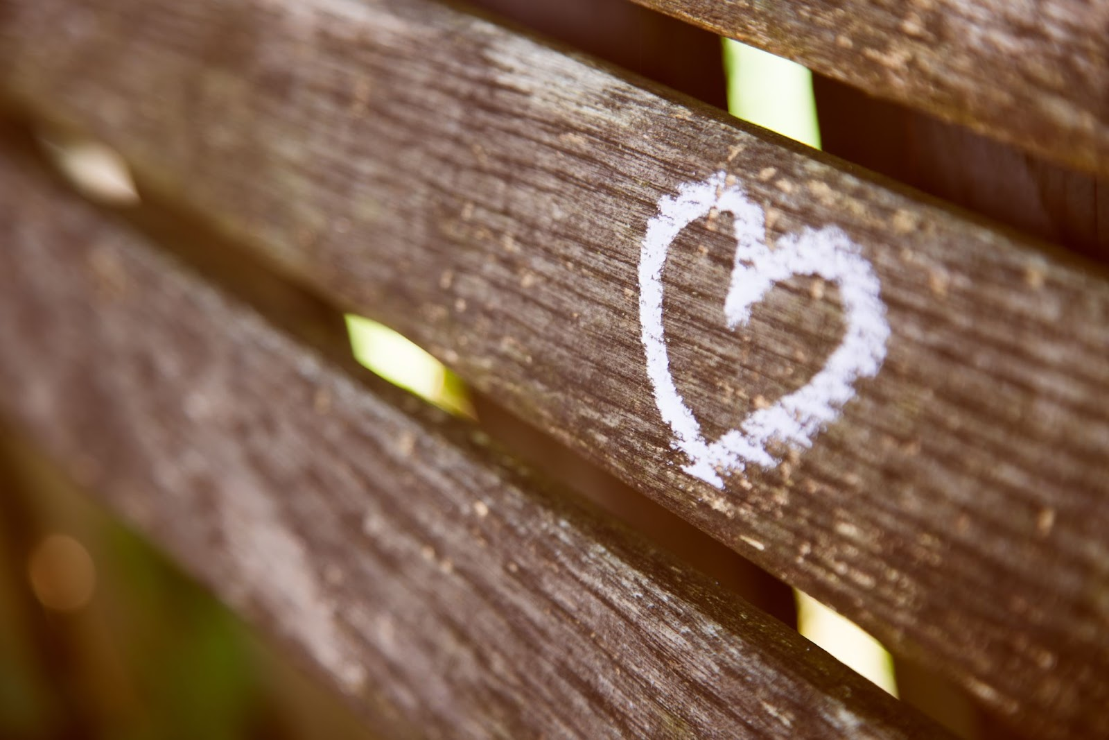 A white heart drawn on a wooden bench