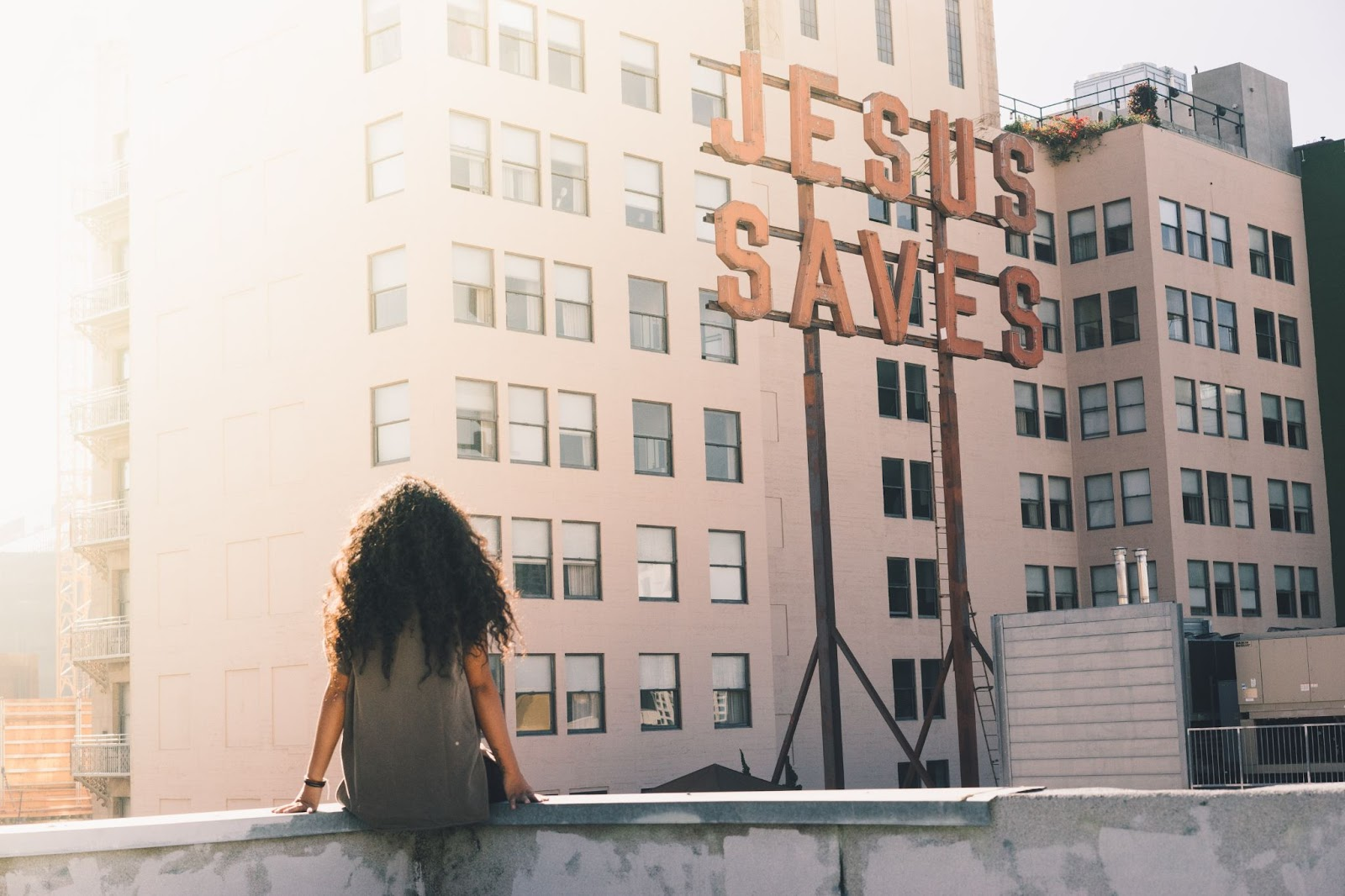 Girl sitting on a wall under a sign that says 'Jesus Saves'