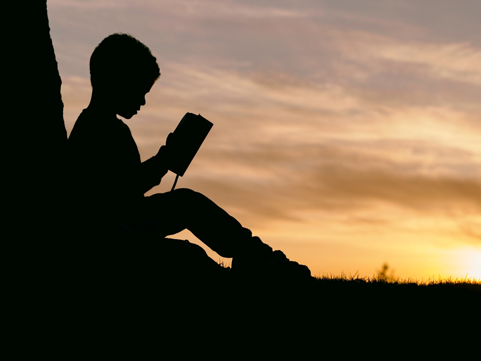 silhouette of a child reading the Bible