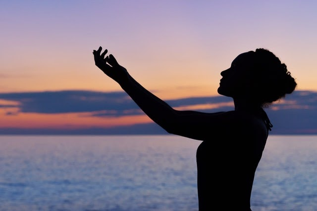 Woman's hands confidently outstretched in prayer