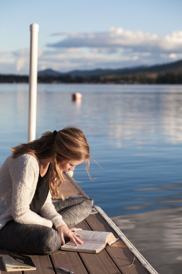 Woman reading Bible by the water's edge