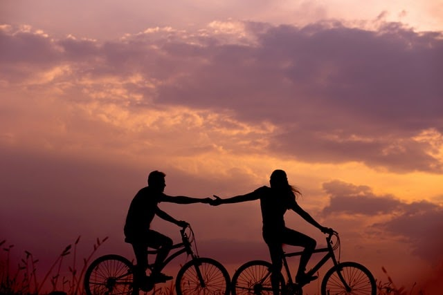 Loving couple cycling at sunset