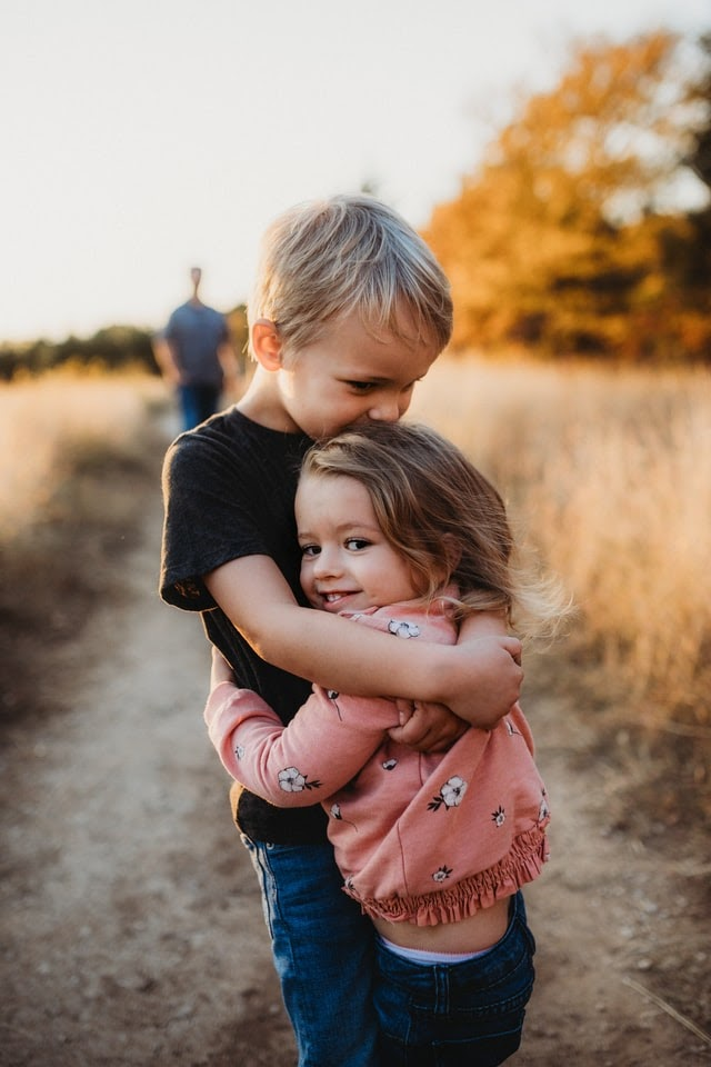 Family love - small boy hugging his sister